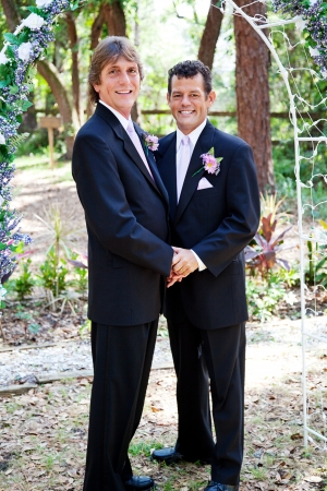 Handsome gay male wedding couple standing under a beautiful floral archway.   Stock Photo
