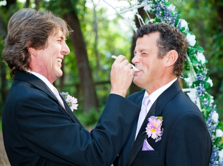 One groom at a gay wedding feeding cake to his husband and laughing.   photo