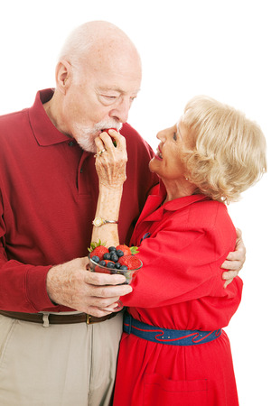 Fit healthy senior couple.  Wife is feeding a strawberry to her husband.  Isolated on white.   photo