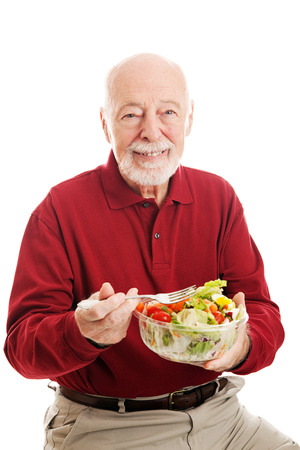 Senior man eating a healthy salad.  Isolated on white background.   photo
