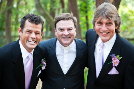 Minister posing with a handsome gay wedding couple he has just married.  *focus is on the minister. photo
