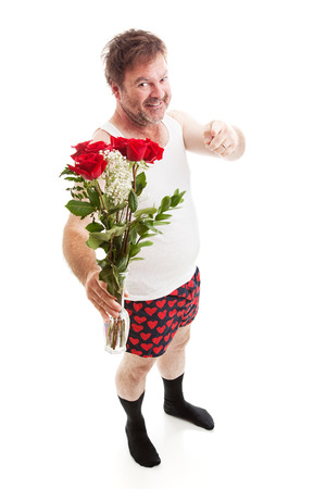 Scruffy looking guy in his underwear with too much confidence holding a vase of red roses and pointing at you. Full body isolated on white.       photo