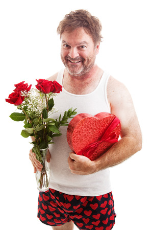 Humorous photo of a scruffy looking middle aged man in his underwear holding a bouquet of roses and a box of Valentines day candy for his sweetie. Isolated on white. Stock Photo