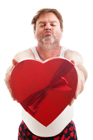 wifebeater: Humorous photo of a scruffy looking middle aged man in his underwear holding a box of Valentines day candy and waiting for a kiss. Isolated on white.