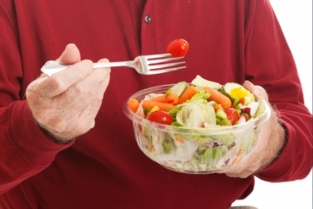 Closeup of a senior man eating a tossed salad.   photo