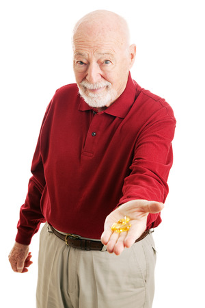 inflamation: Senior man holding out a handful of omega 3 fish oil capsules.  Isolated on white.   Stock Photo
