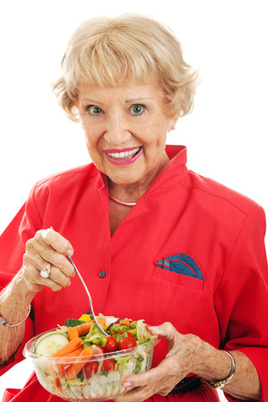 Healthy fit senior woman enjoying a delicious tossed salad.  White background.  photo