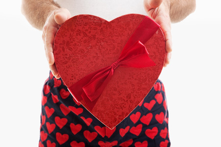 Man in hear underwear holding a big red Valentines Day heart filled with chocolate candy.  White background.   Stock Photo