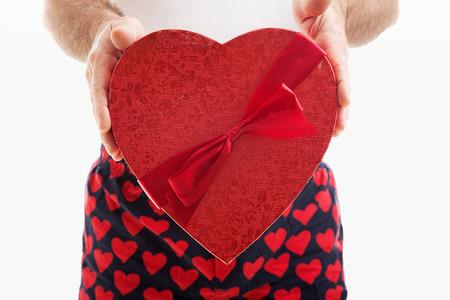 wifebeater: Uomo nel sentire intimo che tiene un grande rosso San Valentino cuore pieno di caramelle al cioccolato. Sfondo bianco.