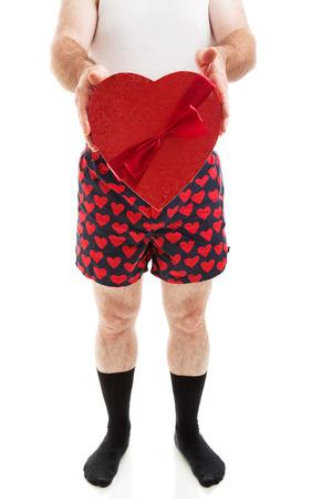 wifebeater: Umorismo foto di un uomo in boxer cuore e calzini neri in possesso di una scatola di caramelle di San Valentino. Isolati su bianco.