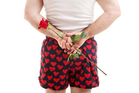 wifebeater: Vista posteriore di un uomo nel cuore boxer in possesso di una rosa rossa per il suo amante dietro la schiena. Sfondo bianco.