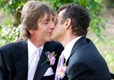 gay men: Hermoso pareja de hombres gay besándose en el parque el día de su boda.