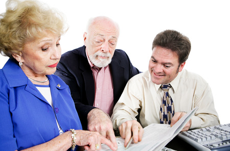 Accountant going over taxes with his senior clients.  Isolated on white.   photo