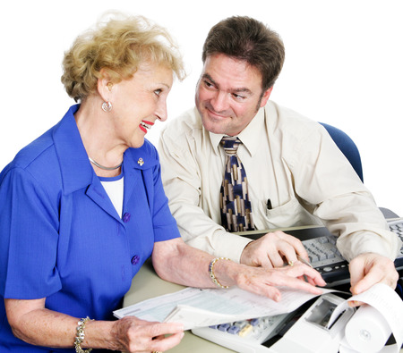 Handsome young accountant helping senior lady with her taxes and financial planning. Imagens