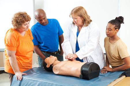 Studenti vzdělávání dospělých učení CPR a první pomoc od lékaře nebo zdravotní sestry. Reklamní fotografie