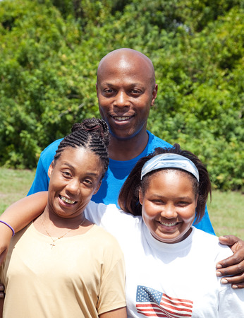 African-american family consisting of father, mother, and adolescent daughter.  Mother has cerebral-palsy. Stock Photo - 25913492
