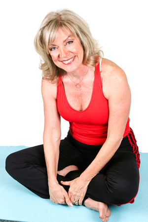 early sixties: Beautiful fit woman in early sixties wearing workout clothes and sitting on her yoga mat.  Isolated on white.   Stock Photo