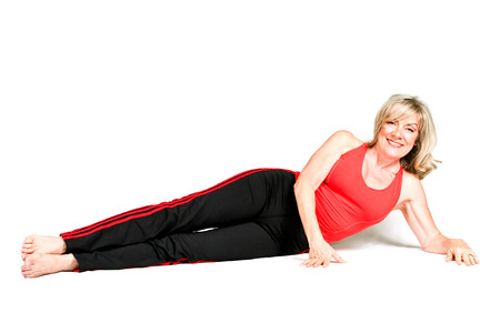 early sixties: Beautiful fitness instructor in her early sixties, looks younger.  Isolated on white.   Stock Photo