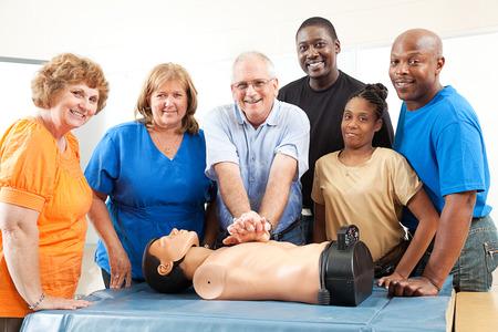 심폐 소생술 및 응급 처치에 성인 교육 클래스입니다. 더미와 학생 및 교사.