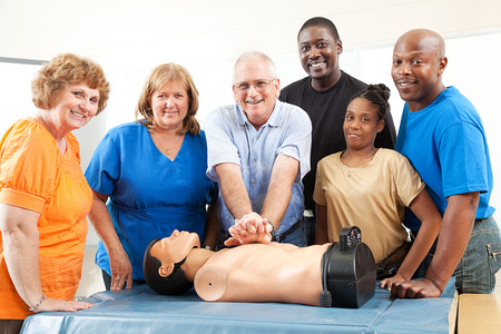 Adult education class on CPR and First Aid.  Students and teacher with dummy.