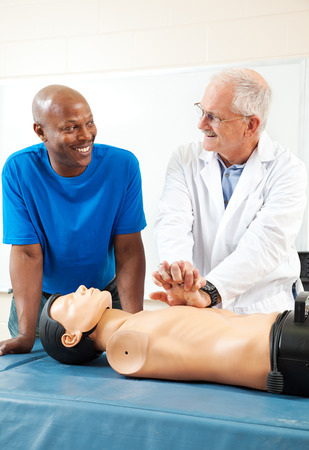 chest compression: African-american adult student learning first aid CPR from a doctor.