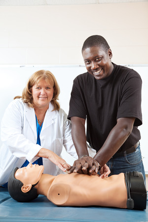 Adult first aid or EMT student practicing CPR on a dummy, with the help of a doctor or nurse.  Vertical with room for text.   photo