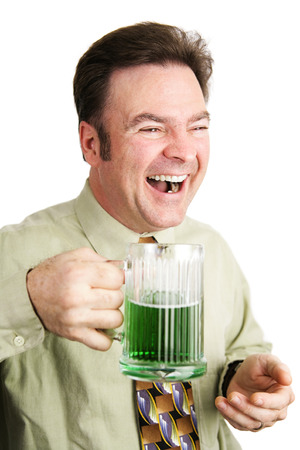 irish ethnicity: Irish American man celebrating St. Patricks Day with a green beer and laughing.  Isolated on white.