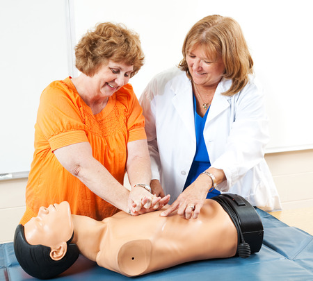 overweight students: Adult education student learning CPR first aid with the help of a doctor or nurse.   Stock Photo