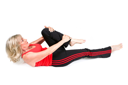 early sixties: Beautiful woman in her early sixties doing stretching exercises to help her back pain.  Isolated on white.