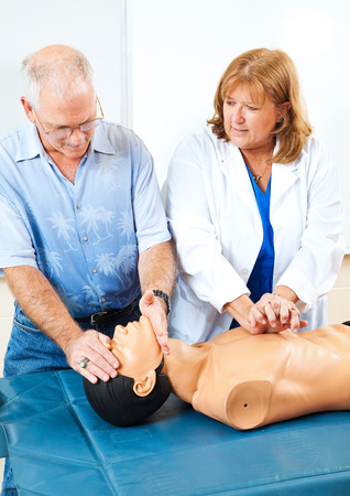 chest compression: Doctor teaching first aid CPR to a mature adult student using a mannequin.   Stock Photo