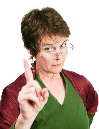 disapproval: Bossy looking middle-aged woman wagging her finger in disapproval.  Isolated on white.