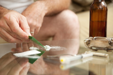 snort: Man using powdered cocaine on a glass coffee table, with drug paraphanalia lying around.