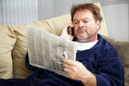 Unemployed man at home on the couch looking at the classified ads in the newspaper.   Stock Photo