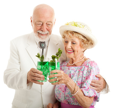 kentucky derby: Southern senior couple enjoying traditional mint julep coctails to celebrate the Kentucky Derby.  Isolated on white.   Stock Photo