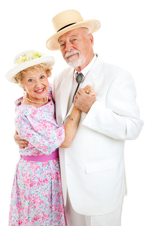 Loving senior couple in Southern style clothing dancing together.  White background.   Foto de archivo