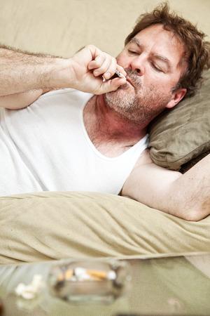 wifebeater: Met� anni uomo in mutande sballando sul suo divano di casa. Archivio Fotografico