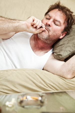 Middle aged man in his underwear getting high on his couch at home.   Stock Photo