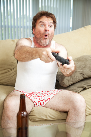 unemployed: Man on the couch playing a video game in his underwear. Beer bottle in foreground.