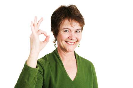 irish ethnicity: Pretty mature Irish woman making the Okay sign with her hands.  Isolated on white.