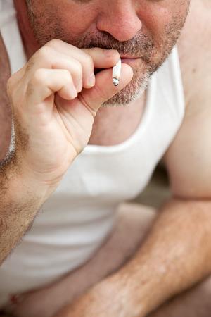 wifebeater: Closeupr di un uomo di mezza et� fumare uno spinello. Il consumo di droga tema o legalizzazione. Archivio Fotografico