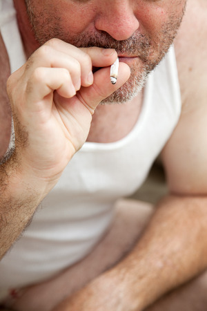 drug use: Closeupr of a middle-aged man smoking a joint.  Drug use theme or legalization.   Stock Photo