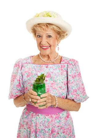 kentucky: Beautiful senior Southern Belle drinking a traditional mint julep to celebrate Kentucky Derby day.  Isolated on white.