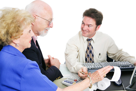 Senior couple going over their taxes with an accountant.  White background.   photo