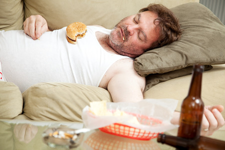 wifebeater: Scruffy uomo disoccupato svenuto sul divano in mutande, circondato da sigarette, cibo spazzatura e bottiglie di birra.
