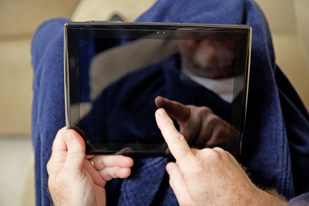 house robe: Closeup of a mans hands usng a tablet PC on the couch in his bathrobe.