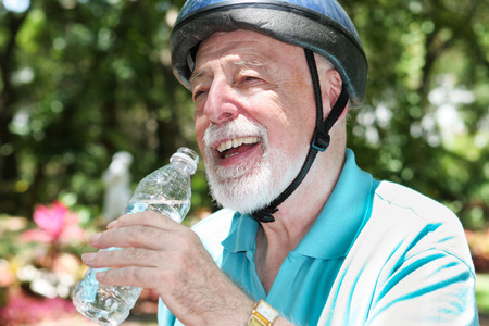 safe water: Active senior man wearing a bicycle helmet stops to drink bottled water.   Stock Photo