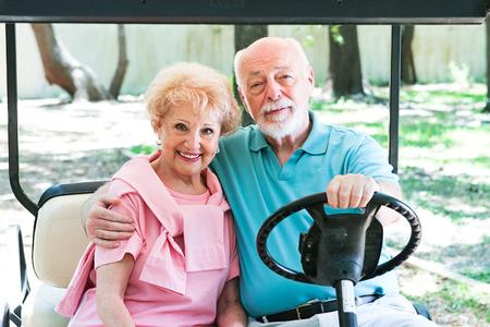senior couple riding around in a golf cart.