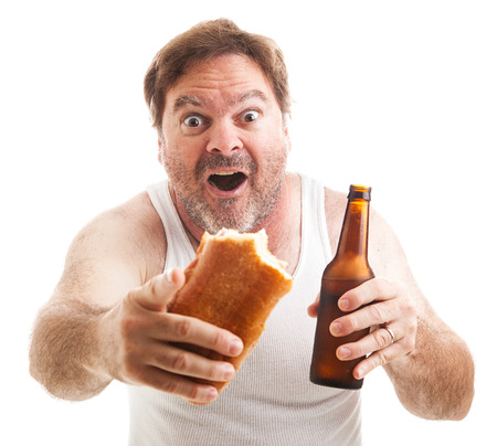 Scruffy man watching a sporting event, holding a sub sandwich and a beer.  Isolated on white.   Stock Photo