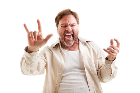 air guitar: Middle-aged man rocks out playing air guitar and making the rock-n-roll symbol.  Isolated on white.