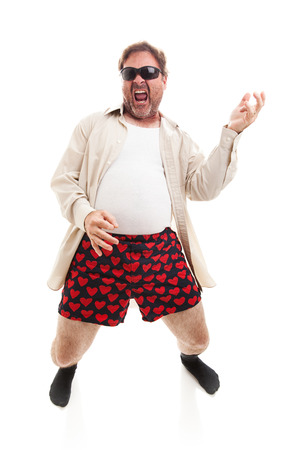 satire: Funny photo of a middle aged man playing air guitar in his underwear.  Full body isolated on white.   Stock Photo